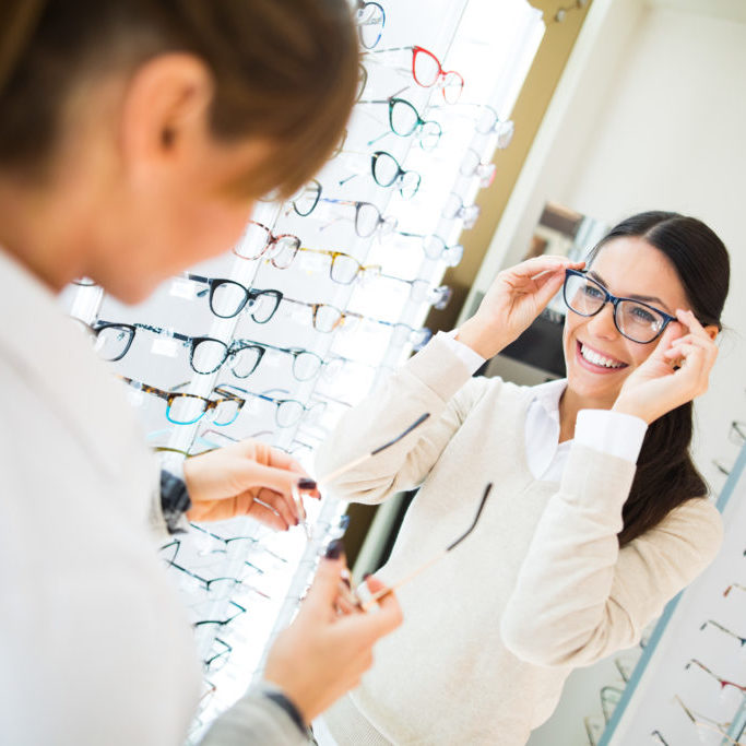 Young smiling woman is trying on eyeglasses in optical shop with the assistance of optometrist.